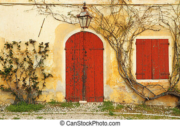 beautiful colorful old doorway with blinded door and window to the rural tuscan house, Italy, Europe