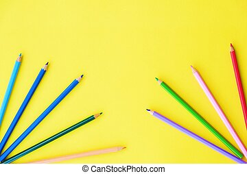 Beautiful colorful pencils on yellow background view