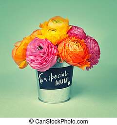 Beautiful colorful ranunculus flowers in a labeled bucket with t