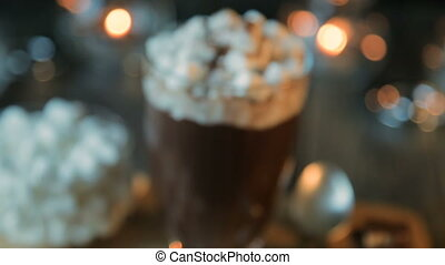 Beautiful composition - hot chocolate with marmalade and chocolate pieces in a transparent glass. The glass stands on a wooden stand. Behind the candles are burning. Close up