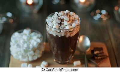 Beautiful composition - hot chocolate with marmalade and chocolate pieces in a transparent glass. The glass stands on a wooden stand. Behind the candles are burning