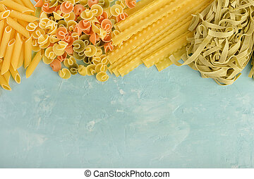 Beautiful composition of pasta with space for text, copy space. Penne, Mafalde, Tagliatelle, Spaghetti laid out on top of a blue background.