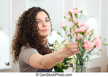Beautiful concentrated young woman florist making bouquet in shop