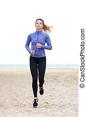 Beautiful confident female jogger in sand