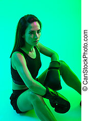 Beautiful confident young fitness girl wearing boxing gloves