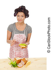 Beautiful cooking woman in apron with sandwich.