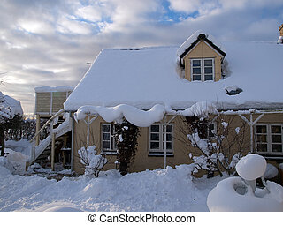 Beautiful traditional country house home in winter covered with snow