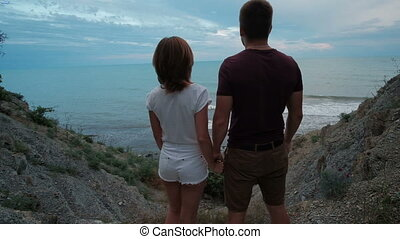Beautiful couple are standing and kissing on scenic coast in summer day outdoor.