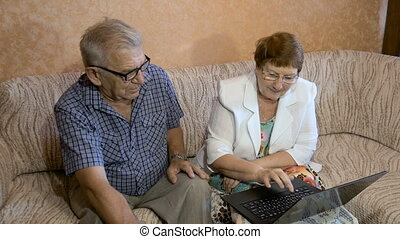 Beautiful couple at the age of working on the laptop at home.