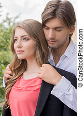 Beautiful couple. Beautiful young couple standing close to each other while man covering woman with his suit