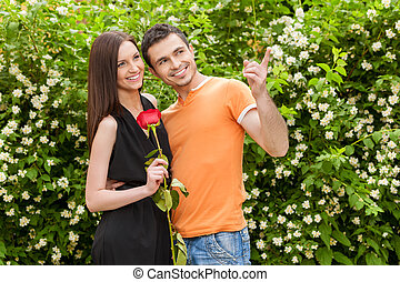 Beautiful couple. Cheerful young couple standing close to each other while man pointing away and smiling