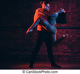 Beautiful couple dancing on the dance floor in a night club....