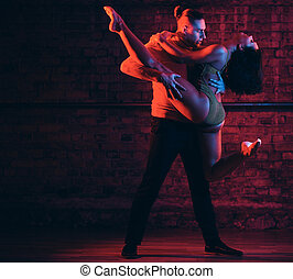 Beautiful couple dancing on the dance floor in a night club. Dancers performing in the dark with illumination