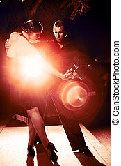 Beautiful couple dancing tango on night street, dramatic light.