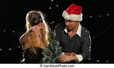 beautiful couple decorating a Christmas tree on Black