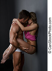 Beautiful couple embracing passionately in studio