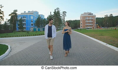 Beautiful couple enamored young people holding hands and strolling on the pretty residential area.