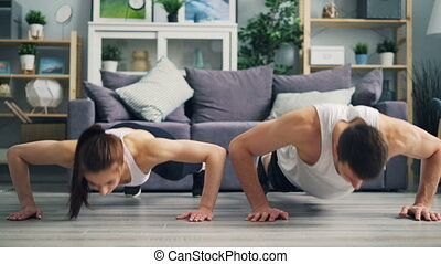 Beautiful couple exercising together doing pushups and...
