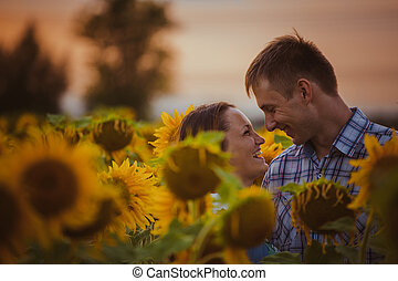 Beautiful couple having fun in sunflowers fields