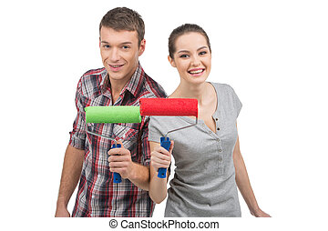 beautiful couple holding painting rollers. man and woman...