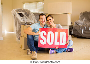 couple holding sold sign surrounded by cardboard boxes