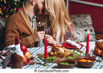 Beautiful couple in a decorated festive interior with a Christmas tree drinking wine. A romantic dinner for thanksgiving with fried chicken and candles