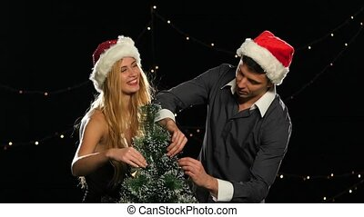 beautiful couple in Christmas hats decorating a Christmas tree on Black