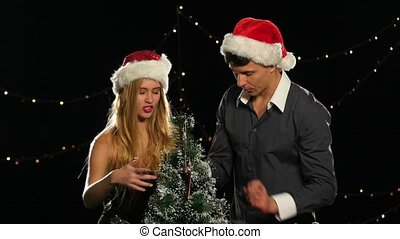 beautiful couple in Christmas hats decorating a Christmas tree together