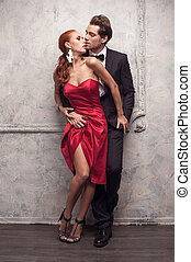 Beautiful couple in classical outfits. Standing and kissing with passion
