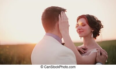 Beautiful couple in love kiss in the nature on their wedding day in summertime. Wonderful sunset in countryside.