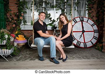 Beautiful couple in love sitting on swing at studio