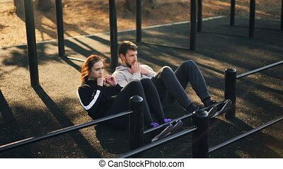 Beautiful couple is doing sports outdoors doing sit-ups...