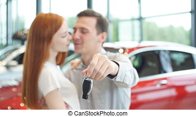 Beautiful couple is holding key of their new car, looking at camera and smiling