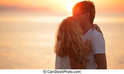 beautiful couple kisses at sunrise