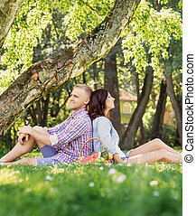 Beautiful couple leaning on each other backs and having a picnic
