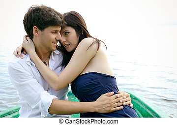 Beautiful couple looking at each other on wood boat