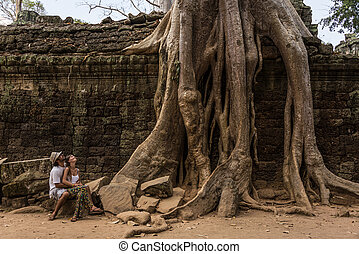 Beautiful Couple looking at Giant Roots at Angkor Wat Cambodia.