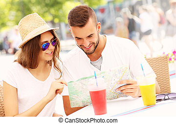 Beautiful couple looking at map in a cafe