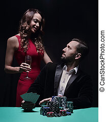 beautiful couple looking at playing cards at poker