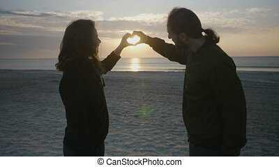 Beautiful couple making heart shape with their hands on the beach at sunrise and then holding their hands and kissing