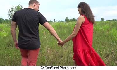 Beautiful couple man and pregnant woman with long hair in a red dress. family.