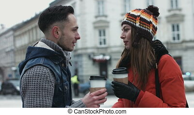 Beautiful couple meet outdoors. Man and woman drinking takeaway coffee on the street and have a nice talk.