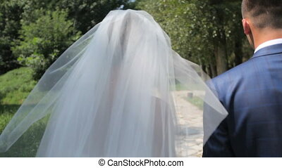 beautiful couple of newlyweds walking in the park.