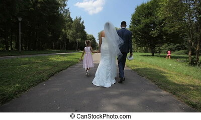 beautiful couple of newlyweds walking in the park with a little girl.