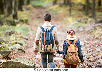 Beautiful couple on a walk in autumn forest