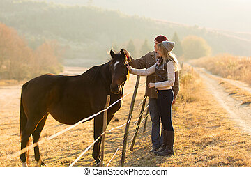 couple petting horse - beautiful couple petting horse in the...