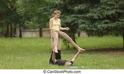 Beautiful couple practicing acro yoga. Young yoga instructors practice in a city park on green grass. Two successful young people perform acro yoga exercises. Man and a woman learn yoga at sunset.