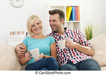 Beautiful couple relaxing on sofa with cup of coffee