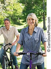 Beautiful couple riding bicycles in park