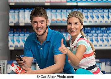 Beautiful Couple Showing Thumbs Up Sign In Supermarket -...
